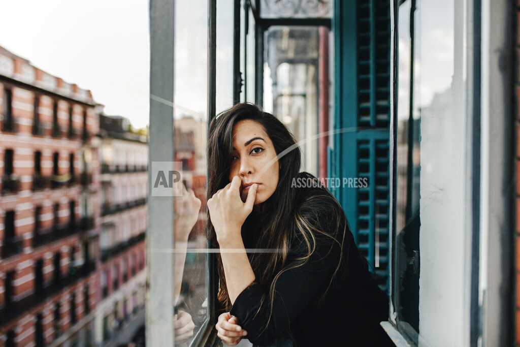 Lonely young woman leaning on glass window