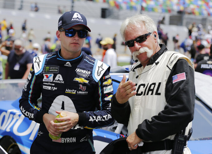 William Byron, left, talks with an official on pit road before a NASCAR auto race at Daytona International Speedway on Sunday, July 7, 2019, in Daytona Beach, Fla. (AP Photo/Terry Renna)