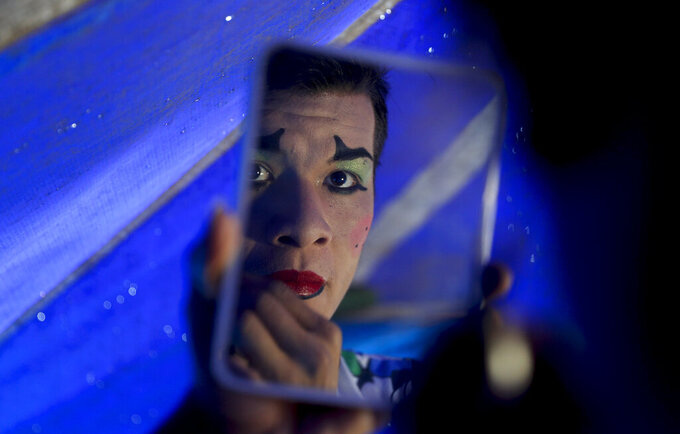 Jumbo Circus clown Franklin Parada, 22, puts on his clown face to train at the circus, even though it's been closed for four months in El Alto, Bolivia, Friday, June 26, 2020. To get by, Parada makes money offloading rice bags from trucks at a street fair. (AP Photo/Juan Karita)
