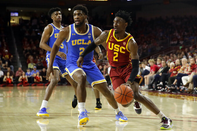Southern California guard Jonah Mathews, right, dibbles next to UCLA forward Cody Riley, center, during the first half of an NCAA college basketball game Saturday, March 7, 2020, in Los Angeles. (AP Photo/Marcio Jose Sanchez)
