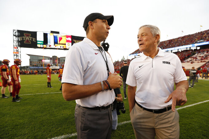 FILE - In this Sept. 14, 2019, file photo, Iowa State head coach Matt Campbell, left, talks with Iowa head coach Kirk Ferentz before an NCAA college football game in Ames, Iowa. Ferentz has been where Campbell is now in his career. Successful coach, courted annually by other schools and the NFL. Ferentz stayed at Iowa and settled into a two-decade run. Heading into the biggest Iowa-Iowa State game in the history of the rivalry, it's hard to know how much longer Campbell will be in Ames. (AP Photo/Charlie Neibergall, File)