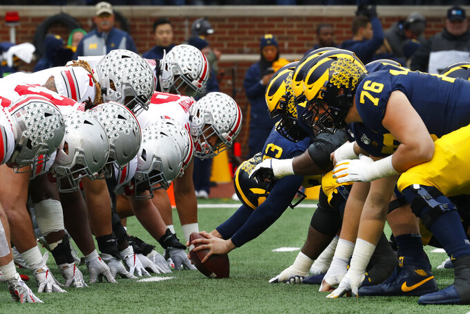 FILE- In this Nov. 30, 2019, file photo, Ohio State, left, and Michigan players line up at the line of scrimmage in the first half of an NCAA college football game in Ann Arbor, Mich. The Big Ten's third football schedule of the 2020 season is highlighted by Michigan-Ohio State on Dec. 12, the final day of the conference's regular-season and the latest date the rivals have ever played.(AP Photo/Paul Sancya, File)