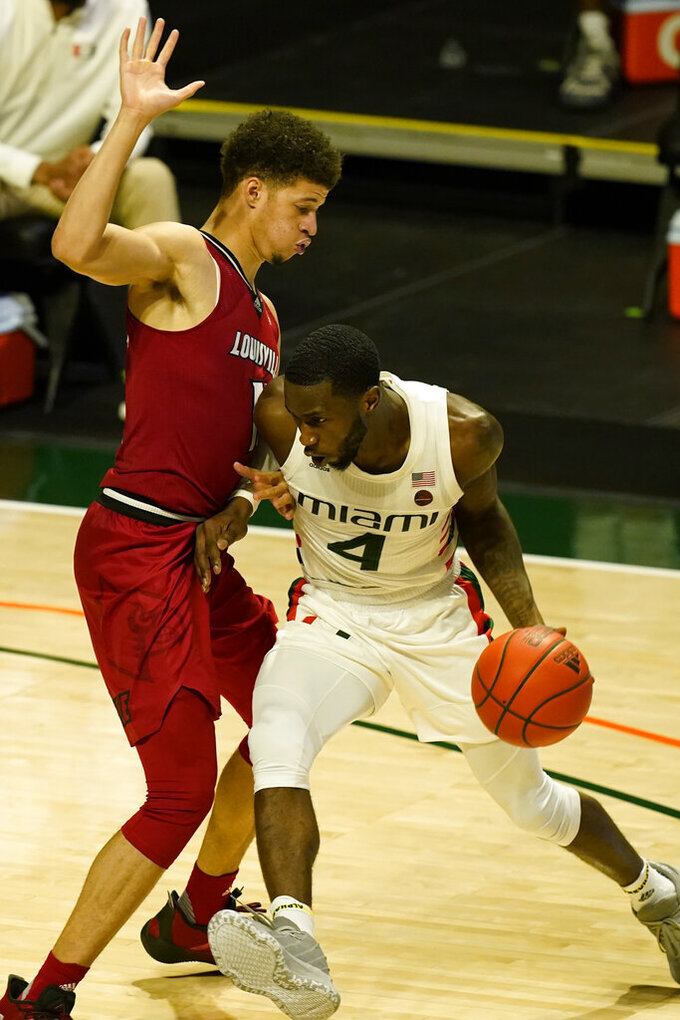 Louisville center Samuell Williamson (10) defends Miami guard Elijah Olaniyi (4) during the second half of an NCAA college basketball game, Saturday, Jan. 16, 2021, in Coral Gables, Fla. Miami defeated Louisville 78-72. (AP Photo/Marta Lavandier)