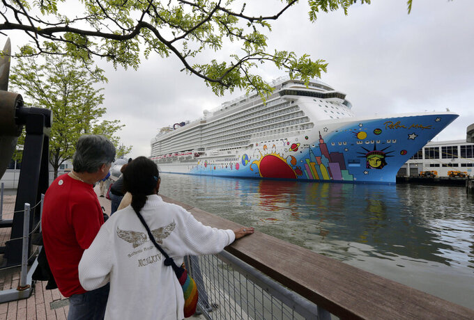 FILE - In this May 8, 2013, file photo, people pause to look at Norwegian Cruise Line's ship, Norwegian Breakaway, on the Hudson River, in New York. On Monday, April 5, 2021, Norwegian Cruise Line's parent company asked the Centers for Disease Control and Prevention for permission to resume cruises from U.S. ports on July 4 by requiring passengers and crew members to be vaccinated against COVID-19 at least two weeks before the trip. (AP Photo/Richard Drew, File)