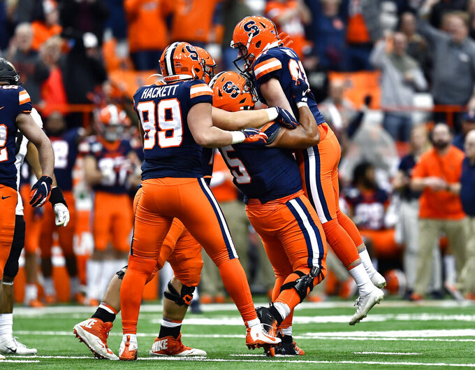 Syracuse kicker Andre Szmyt, right, is lifted into the air by fullback/tight end Chris Elmore (5) after his field goal gave the Orangemen the lead late in the second half of an NCAA college football game against Wake Forest in Syracuse, N.Y., Saturday, Nov. 30, 2019. Syracuse won 39-30 in overtime. (AP Photo/Adrian Kraus)
