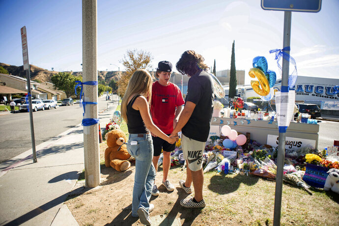 Students Britney Hopkins, Evan Jabbaz and Connor Nassry, all 16, pray at a memorial, Monday, Nov. 18, 2019, for two students killed during a shooting at Saugus High School in Santa Clarita, Calif., several days earlier. Students will return to school on Dec. 2. (Sarah Reingewirtz/The Orange County Register via AP)