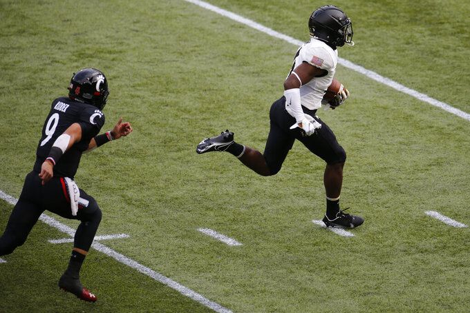 Army defensive back Jabari Moore, right, outruns Cincinnati quarterback Desmond Ridder to the end zone after intercepting Ridder's pitch during the first half of an NCAA college football game Saturday, Sept. 26, 2020, in Cincinnati, Ohio. Moore scored a touchdown on the play. (AP Photo/Jay LaPrete)