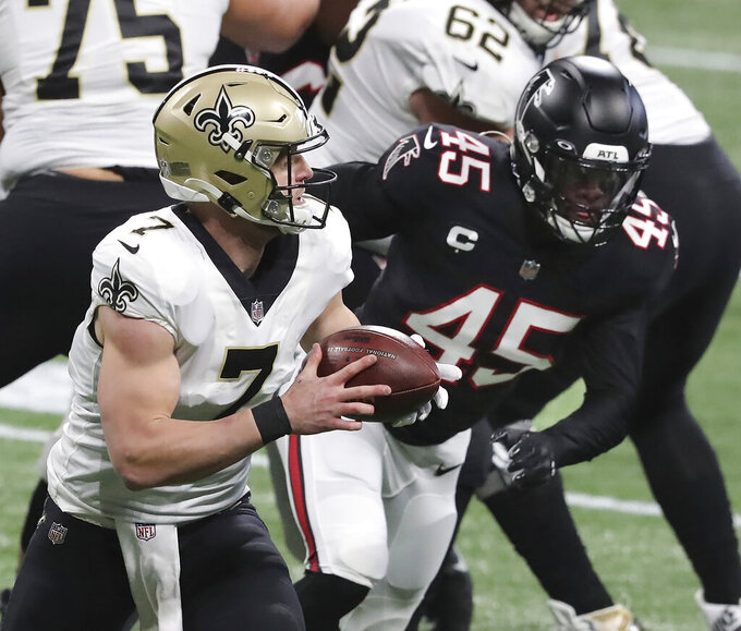 New Orleans Saints quarterback Taysom Hill breaks away from Falcons linebacker Deion Jones for a long gain into Falcons territory to setup a touchdown pass on the next play to Tre'Quan Smith to take a 7-0 lead during the first quarter in a NFL football game on Sunday, Dec. 6, 2020, in Atlanta. (Curtis Compton/Atlanta Journal-Constitution via AP)
