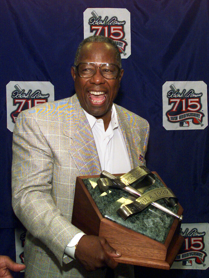 FILE - In this April 8, 1999, file photo, Major League Baseball's all-time career home run record holder Hank Aaron laughs as he shows off the newly unveiled