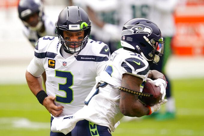 Seattle Seahawks quarterback Russell Wilson (3) hands the ball to running back Chris Carson (32) as they practice before the start of an NFL football game against the Washington Football Team, Sunday, Dec. 20, 2020, in Landover, Md. (AP Photo/Andrew Harnik)