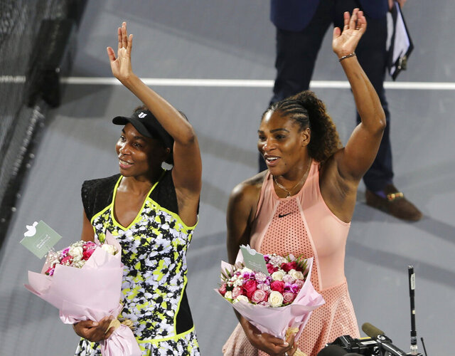 FILE - In this Dec. 27, 2018, file photo, Venus Williams, left, celebrates winning against her sister Serena, right, after a match on the opening day of the Mubadala World Tennis Championship in Abu Dhabi, United Arab Emirates. Serena Williams is looking forward to getting back to competing on a tennis court when the coronavirus pandemic permits it. Her older sister, Venus, is looking forward to hanging out at a rooftop bar. Two of the most famous and successful siblings in the history of sports shared those thoughts and more Tuesday, May 12, 2020, after doing some yoga together during an online session that offered workout tips and some laughs. (AP Photo/Kamran Jebreili, File)