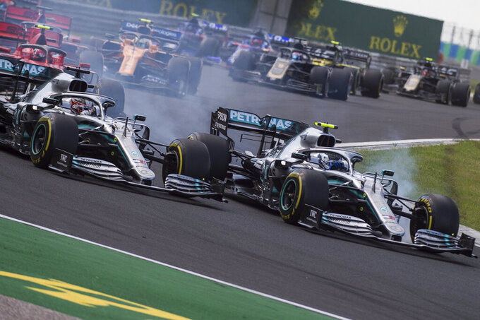 British Forumla One driver Lewis Hamilton of Mercedes, left, and his Finnish teammate Valtteri Bottas steer his car during the Hungarian Formula One Grand Prix at the Hungaroring circuit, in Mogyorod, Hungary, Sunday, Aug. 4, 2019. (Zoltan Balogh/MTI via AP)