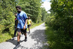 Jamil Boykin, front, camp educator at Mass Audubon's Boston Nature Center and Wildlife Sanctuary, walks with students Giovanni Pierre, left, and Aaron Overton, right, during a hike at the sanctuary, in the Mattapan neighborhood of Boston, Wednesday, June 23, 2021. Audubon Society chapters are grappling with how to address their namesake's legacy as the nation continues to reckon with its racist past. John James Audubon was a celebrated 19th century naturalist but also a slaveholder publicly opposed to abolition. (AP Photo/Steven Senne)