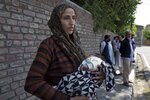 Ulfat, a Kashmiri woman holds her forty days old daughter Tanzeela, as she waits outside a police station to hear about her husband who was detained during night raids in Srinagar, Indian controlled Kashmir, Tuesday, Aug. 20, 2019. Authorities say thousands of people, mostly young male protesters, have been arrested and detained in Indian-administered Kashmir amid an ongoing communications blackout and security lockdown. (AP Photo/ Dar Yasin)
