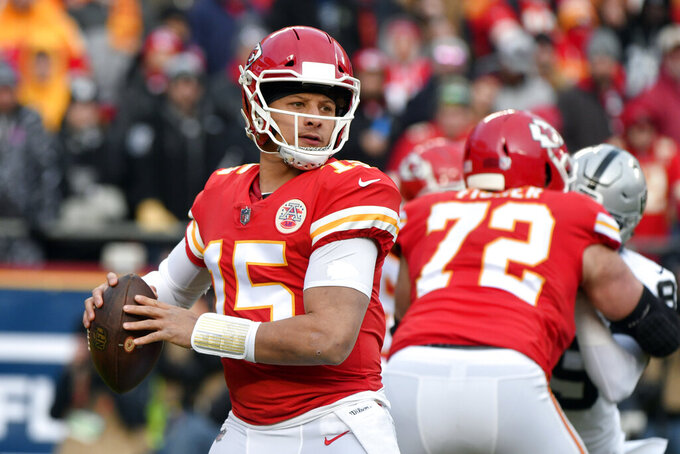FILE - In this Dec. 30, 2018 file photo Kansas City Chiefs quarterback Patrick Mahomes (15) looks for a receiver during the first half of an NFL football game against the Oakland Raiders in Kansas City, Mo. The Chiefs have never beaten Indianapolis in four tries in the playoffs. They will try to end that era of heartache in the divisional round on Saturday, Jan. 12, 2019. Patrick Mahomes and the Chiefs' record-setting offense may have to outscore Andrew Luck and the Colts, who hope to put up big numbers against a suspect Kansas City defense at Arrowhead Stadium. (AP Photo/Ed Zurga, file)