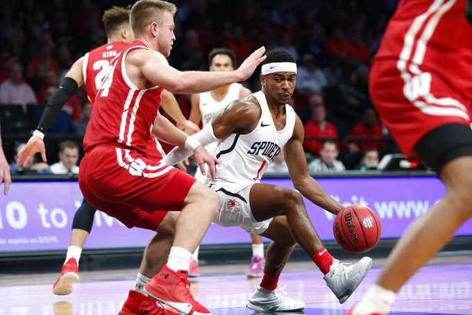 Richmond guard Blake Francis (1) drives around Wisconsin guard Brad Davison (34) during the second half of an NCAA college basketball game in the Legends Classic, Monday, Nov. 25, 2019, in New York. Richmond defeated Wisconsin 62-52. (AP Photo/Kathy Willens)
