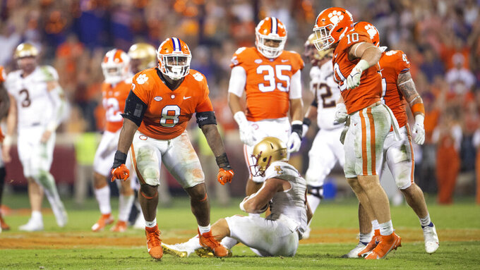 Clemson defensive tackle Tre Williams (8) and linebacker Baylon Spector (10) react after sacking Boston College quarterback Dennis Grosel, bottom center, during the second half of an NCAA college football game Saturday, Oct. 2, 2021, in Clemson, S.C. (AP Photo/Hakim Wright Sr.)