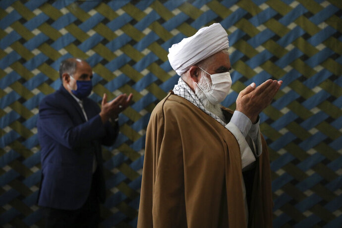 A cleric wearing a protective face mask to help prevent the spread of the coronavirus, leads the noon prayer at a mosque in the the city of Zanjan, some 330 kilometers (205 miles) west of the capital Tehran, Iran, Sunday, July 5, 2020. Iran on Sunday instituted mandatory mask-wearing as fears mount over newly spiking reported deaths from the coronavirus, even as its public increasingly shrugs off the danger of the COVID-19 illness it causes. (AP Photo/Vahid Salemi)