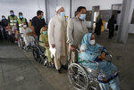 Senior citizens wait their turn to receive the Sinopharm coronavirus vaccine from a health worker at a vaccination center in Lahore, Pakistan, Thursday, March 18, 2021. Pakistan has started vaccinating people who are 60 years old or above amid a steady increase in cases and fatalities from the disease. (AP Photo/K.M. Chaudary)