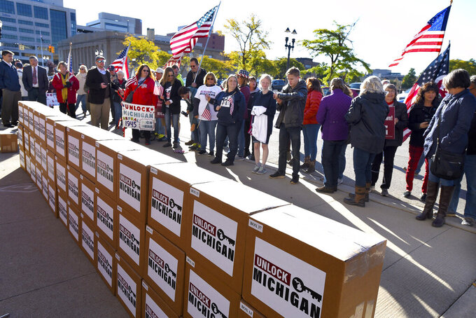 FILE - In this Oct. 2, 2020 file photo, a group gathers as boxes filled with petition signatures are delivered by Unlock Michigan to the Michigan Department of State Bureau of Elections in Lansing, Mich. A group trying to repeal an emergency powers law that Gov. Gretchen Whitmer used for months to issue coronavirus restrictions cleared a key hurdle Monday, April 19, 2021 when the Michigan elections bureau said it collected enough petitions. (Rod Sanford/Detroit News via AP)