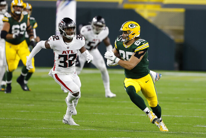 Green Bay Packers' Robert Tonyan (85) is pursued by Atlanta Falcons' Jaylinn Hawkins (32) during the first half of an NFL football game, Monday, Oct. 5, 2020, in Green Bay, Wis. (AP Photo/Tom Lynn)