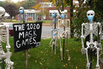 Coronavirus-themed Halloween decorations are displayed on a lawn in Tenafly, N.J., Thursday, Oct. 22, 2020. New Jersey's climbing number of COVID-19 cases are beginning to spread to northern counties around New York, Gov. Phil Murphy said Thursday. Essex, Union, Hudson and Bergen counties reported more than 100 new cases overnight, Murphy said, eclipsing recent hot spots in Ocean and Monmouth counties. (AP Photo/Seth Wenig)