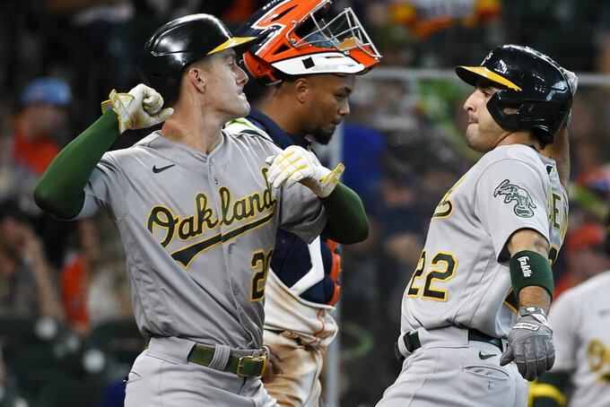 Oakland Athletics' Ramon Laureano, right, celebrates his two-run home run with Mark Canha during the fifth inning of a baseball game against the Houston Astros, Saturday, April 10, 2021, in Houston. (AP Photo/Eric Christian Smith)
