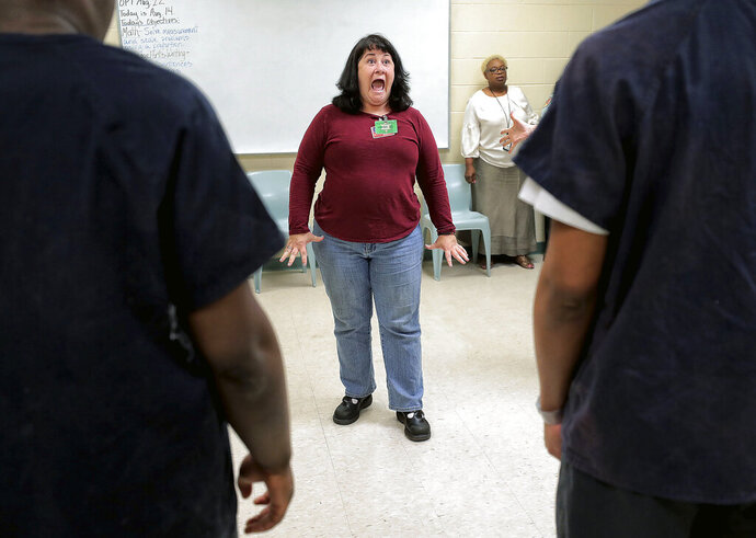 Carmen Mandley, with the Tennessee Shakespeare Company gets her students warmed up with facial excercises while working on a speech project with juveniles being house at Jail East on Aug. 14, 2019 in Memphis. The Tennessee Shakespeare Company has recently received a grant to work with juveniles in Shelby County Juvenile Court. (Jim Weber/Daily Memphian via AP)