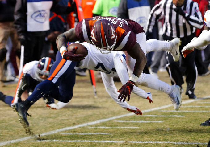 Virginia Tech running back Steven Peoples (32) gets stopped short of the goal line by Virginia safety Brenton Nelson (28) during the first half of an NCAA college football game in Blacksburg, Va., Friday, Nov. 23, 2018. (AP Photo/Steve Helber)