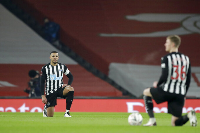 Newcastle's Jamaal Lascelles and Sean Longstaff, right, take the knee before the start of the English FA Cup third round soccer match between Arsenal and Newcastle United at the Emirates Stadium in London, England, Saturday, Jan. 9, 2020. (AP Photo/Matt Dunham)