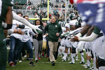FILE - In this April 25, 2015, file photo, with Michigan State football players lined up to greet them, head coach Mark Dantonio leads a group of students onto the field before the Spartans' spring NCAA college football game in East Lansing, Mich. Dantonio announced his retirement Tuesday, Feb. 4, 2020, ending a 13-year run in which he guided the Spartans to heights they hadn't reached in decades. (AP Photo/Al Goldis, File)