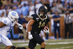 Wake Forest wide receiver Sage Surratt (14) runs after a catch as he is chased by North Carolina defensive back Myles Wolfolk (11) during the first half of an NCAA college football game in Winston-Salem, N.C., Friday, Sept. 13, 2019. (AP Photo/Nell Redmond)
