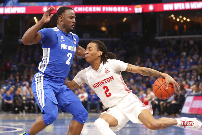 Houston guard Caleb Mills (2) drives the ball past Memphis guard Alex Lomax (2) in the first half of an NCAA college basketball game Saturday, Feb. 22, 2020, in Memphis, Tenn. (AP Photo/Karen Pulfer Focht)