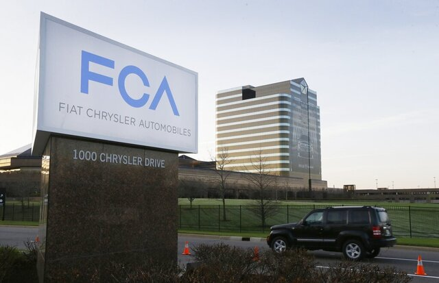 FILE - In this May 6, 2014, file photo, a vehicle moves past a sign outside Fiat Chrysler Automobiles world headquarters in Auburn Hills, Mich. Fiat Chrysler is backing off a planned May 4 restart at its North American factories because some U.S. states still will have stay-home orders in place. The move likely means that factories of all three Detroit automakers will be idled for at least another two weeks as they negotiate reopening terms with the United Auto Workers union. (AP Photo/Carlos Osorio, File)