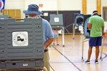 Peter McDonald, left, casts his ballot, Tuesday, July 14, 2020, in Houston. (AP Photo/David J. Phillip)