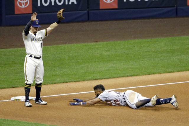 Detroit Tigers' Willi Castro, right, slides in safely at third base past Milwaukee Brewers' Eric Sogard after hitting an RBI-triple during the fourth inning of a baseball game Tuesday, Sept. 1, 2020, in Milwaukee. (AP Photo/Aaron Gash)