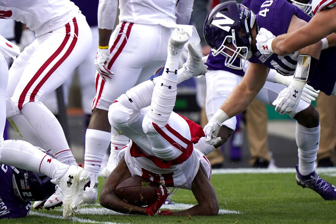 Wisconsin wide receiver Stephan Bracey, left, is tackled by Northwestern linebacker Peter McIntyre during the first half of an NCAA college football game in Evanston, Ill., Saturday, Nov. 21, 2020. (AP Photo/Nam Y. Huh)