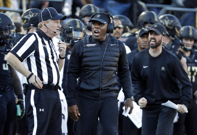 Vanderbilt head coach Derek Mason, center, argues a call in the first half of an NCAA college football game against Tennessee, Saturday, Nov. 24, 2018, in Nashville, Tenn. (AP Photo/Mark Humphrey)