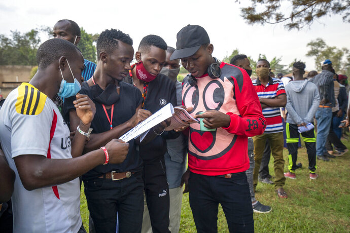 Young Ugandans check the voters listings as they wait to vote in Kampala, Uganda, Thursday, Jan. 14, 2021. Ugandans are voting in a presidential election tainted by widespread violence that some fear could escalate as security forces try to stop supporters of leading opposition challenger BobiWine from monitoring polling stations.(AP Photo/Jerome Delay)