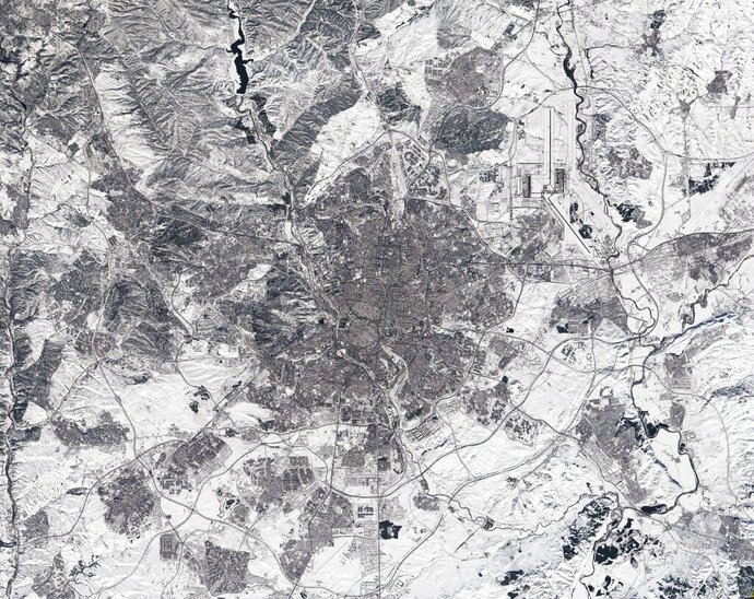 In this photo made available on Tuesday, Jan. 12, 2021, by the European Space Agency, a view of a Copernicus Sentinel-2 image of Madrid, Spain. The image appears to have been taken in black and white. In fact, it is a true-colour image – but the heaviest snowfall in 50 years has blanketed the region, turning the landscape white. Much of Spain is struggling to return to normality three days after a 30-hour-long record snowfall that was then hardened by record-low temperatures, turning streets and roads into dangerous ice sheets in areas not used to extreme winters.  (European Space Agency via AP)