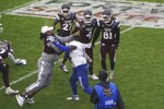 Mississippi State linebacker De'Monte Russell (9) and Tulsa safety TieNeal Martin (7) fight after time runs out in the Armed Forces Bowl NCAA college football game Thursday, Dec. 31, 2020, in Fort Worth, Texas. (AP Photo/Jim Cowsert)