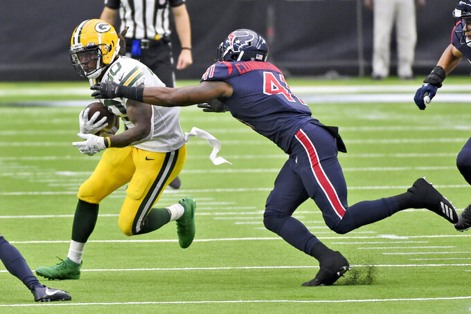 Green Bay Packers running back Jamaal Williams (30) runs with the ball as Houston Texans linebacker Zach Cunningham (41) defends during the second half of an NFL football game Sunday, Oct. 25, 2020, in Houston. (AP Photo/Eric Christian Smith)