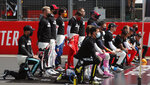 Some drivers take a knee while others stand during an end racism recognition prior to the start of the 70th Anniversary Formula One Grand Prix at the Silverstone circuit, Silverstone, England, Sunday, Aug. 9, 2020. (AP Photo/Frank Augstein, Pool)