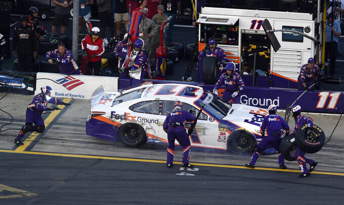 Crew members change tires on Denny Hamlin's car after he brushed the wall during the NASCAR Cup Series auto race at Charlotte Motor Speedway in Concord, N.C., Sunday, May 26, 2019. (AP Photo/Mike McCarn)
