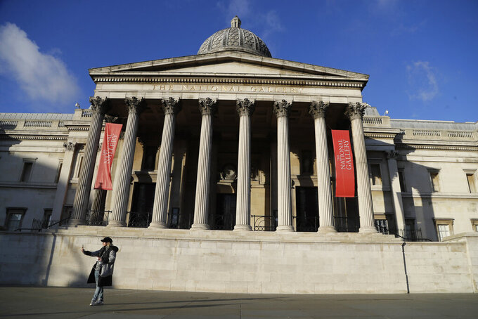 FILE - In this Wednesday, Jan. 6, 2021 file photo, a woman takes a selfie outside the National Gallery of art in London. Tony Hall, who was director of BBC news and current affairs at the time of the public broadcaster's explosive 1995 interview with Princess Diana, resigned Saturday May 22, 2021, as board chairman of Britain's National Gallery. (AP Photo/Kirsty Wigglesworth, File)