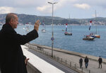 Turkey's President Recep Tayyip Erdogan salutes vessels decorated with Turkish flags as they sail the Bosporus Strait in Istanbul, part of the celebrations for the 567th anniversary of the Ottoman conquest of the city, then known as Constantinople, in 1453, on Friday, May 29, 2020. (Presidential Press Service via AP, Pool)