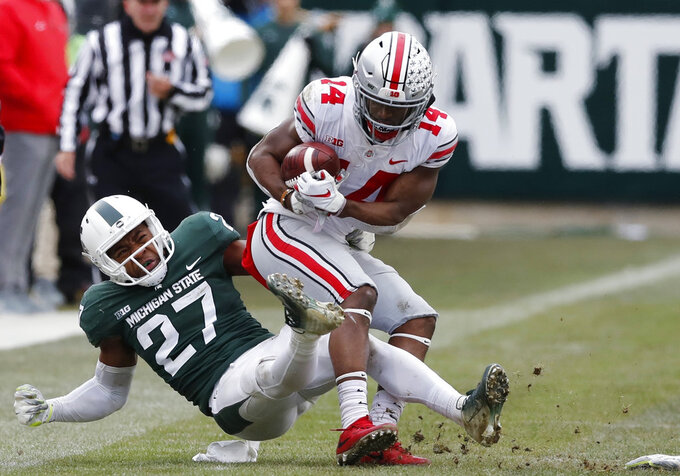 FILE - In this Nov. 10, 2018, file photo, Michigan State safety Khari Willis (27) stops Ohio State wide receiver K.J. Hill (14) during the second half of an NCAA college football game in East Lansing, Mich. In Willis' freshman season, the Spartans won the Big Ten and went to the College Football Playoff. Then the team collapsed to a 3-9 record the following year. Michigan State bounced back to win 10 games in 2017, but this season has been a disappointment the Spartans are barely bowl eligible as they enter their regular-season finale, against Rutgers. (AP Photo/Carlos Osorio, File)
