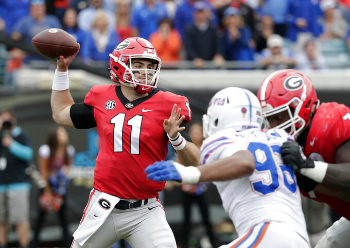 Georgia quarterback Jake Fromm (11) looks to throw a pass as Florida defensive lineman Cece Jefferson, right, rushes during the first half of an NCAA college football game Saturday, Oct. 27, 2018, in Jacksonville, Fla. (AP Photo/John Raoux)