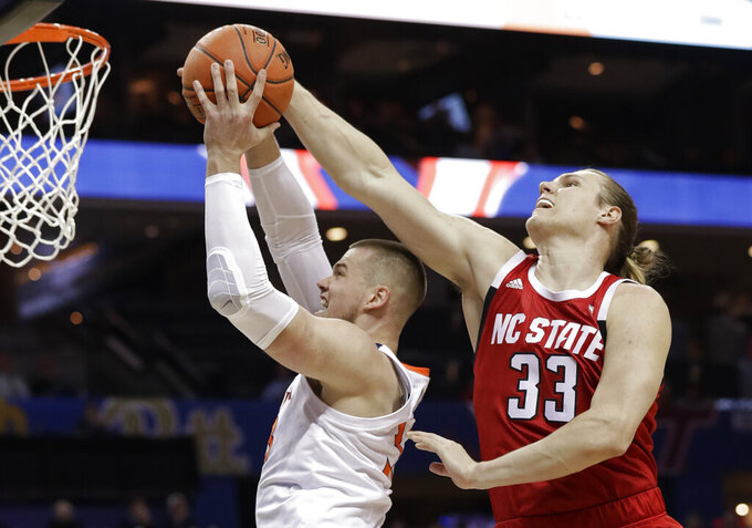 North Carolina State's Wyatt Walker, right, blocks a shot by Virginia's Jack Salt, left, during the first half of an NCAA college basketball game in the Atlantic Coast Conference tournament in Charlotte, N.C., Thursday, March 14, 2019. (AP Photo/Chuck Burton)