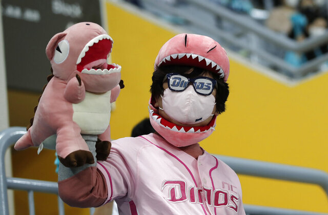 A fan wearing a face mask as a precaution against the coronavirus cheers during Game 2 of the Korean Series, the Korea Baseball Organization's championship round, between Doosan Bears and NC Dinos at Gocheok Sky Dome in Seoul, South Korea, Wednesday, Nov. 18, 2020. (AP Photo/Lee Jin-man)